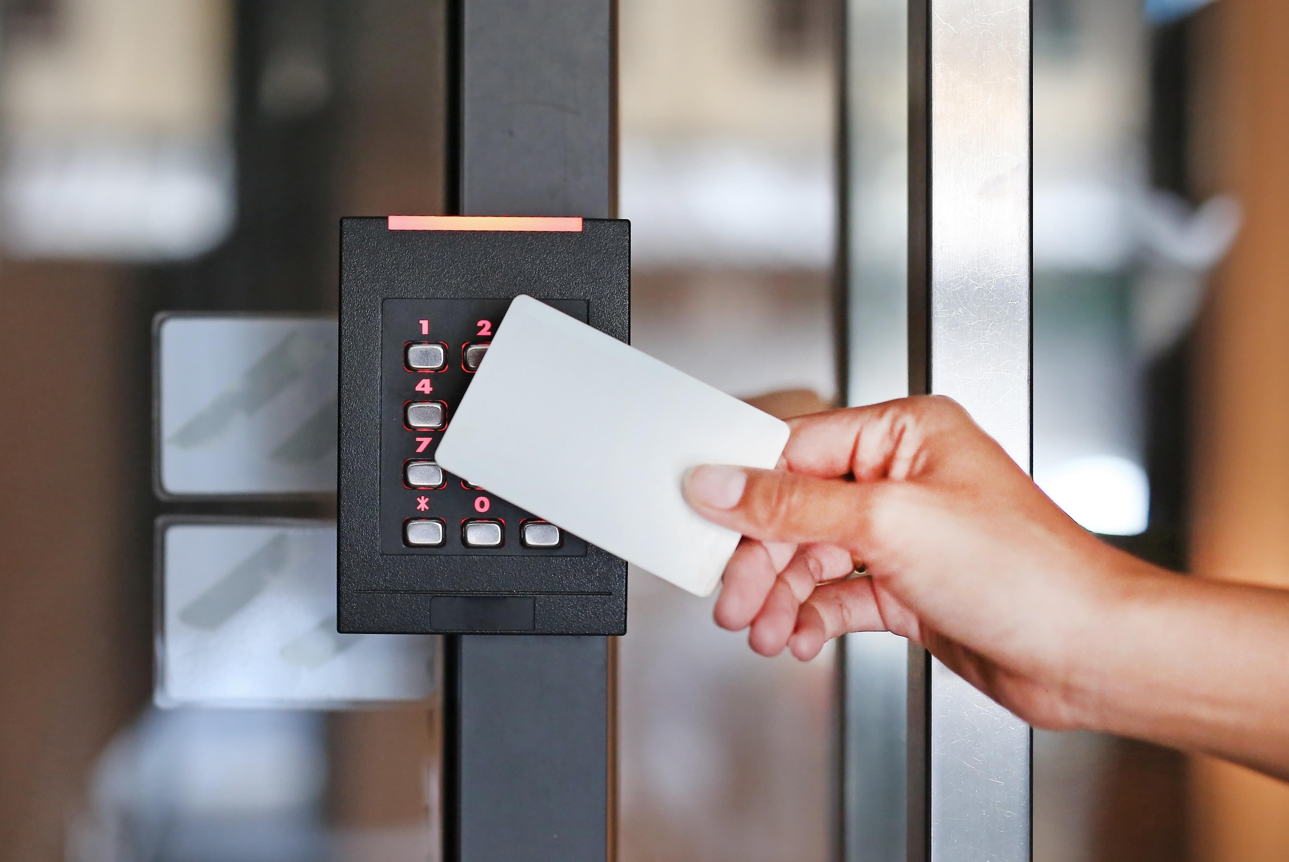 Frau hält eine Chipkarte zur Arbeitszeiterfassung an eine elektronische Stechuhr