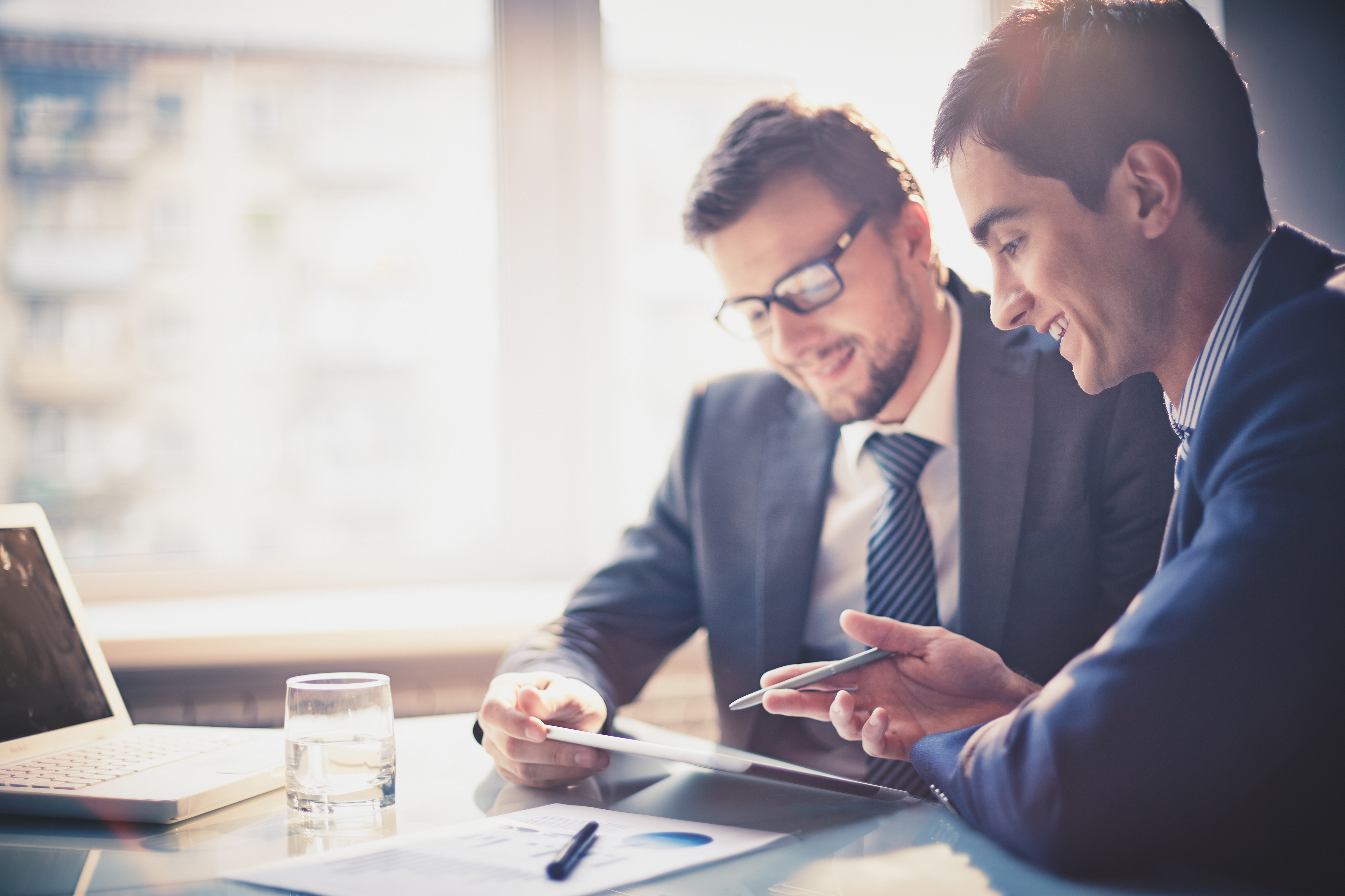Zwei freundlich lächelnde Männer in dunklen Businessanzügen sitzen vor einer hellen Fensterfront an einem Tisch, auf dem Unterlagen liegen und ein Laptop sowie ein Glas Wasser steht. Einer der beiden Männer hält ein Tablet in seiner Hand, während der andere erklärend mit einem Kugelschreiber auf das Display deutet.