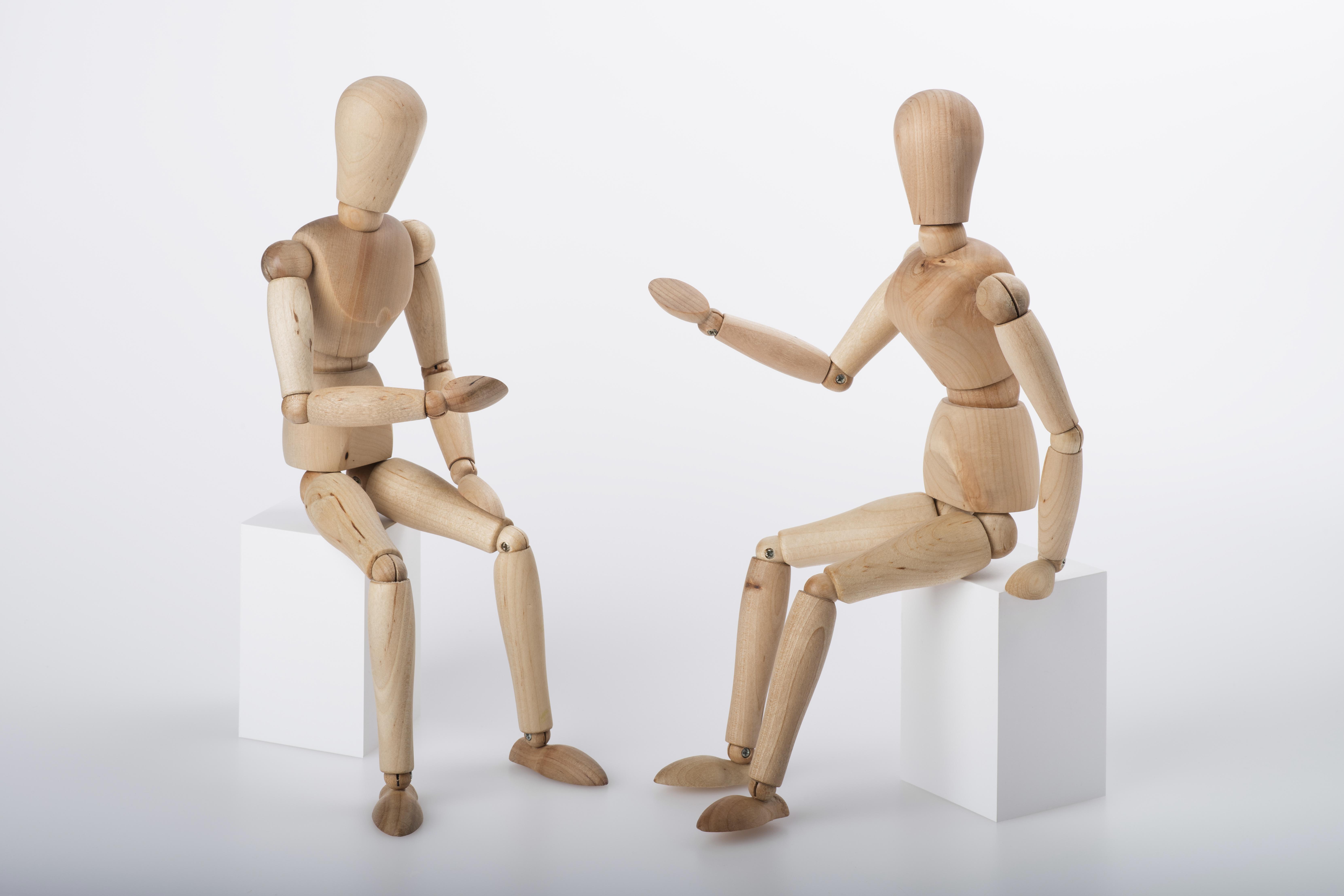Zwei Figuren aus Naturholz mit verstellbaren Gliedern sitzen sich in einer diskutierenden Haltung gegenüber
