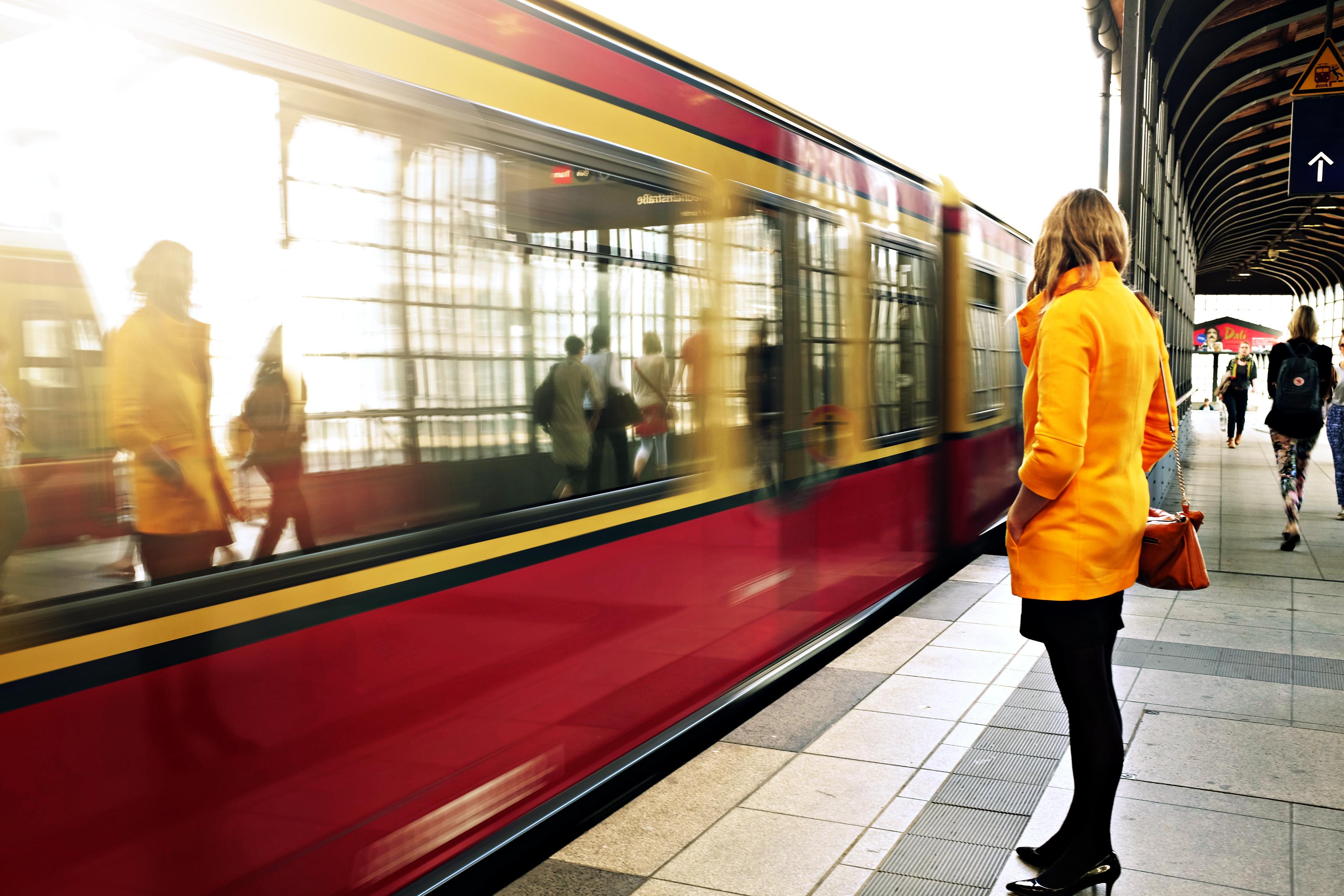 Eine Frau steht am Bahnhof