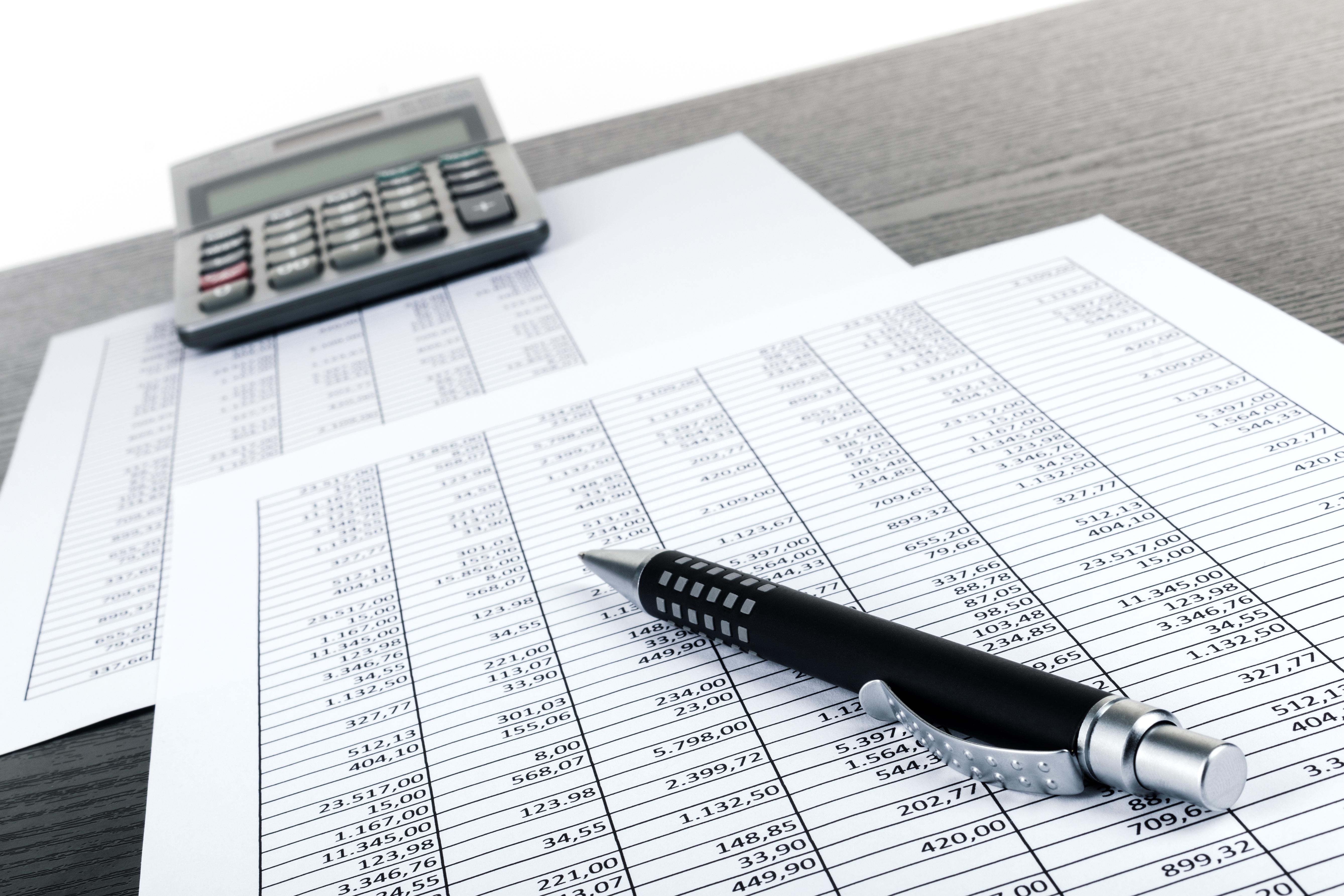 Ein Kugelschreiber und ein Taschenrechner liegen auf einigen mit Tabellen bedruckten Blättern