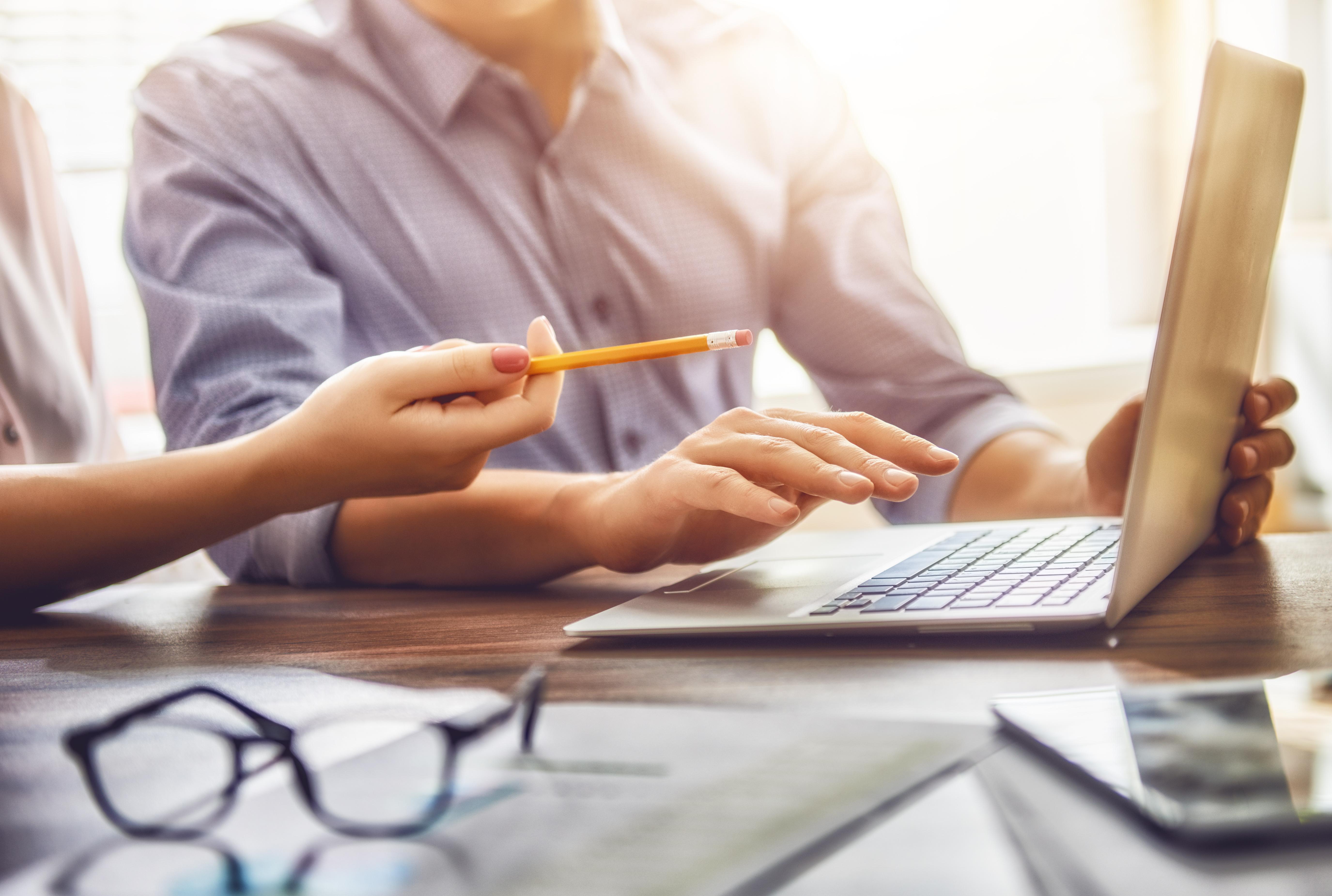 Mann und Frau in Business-Kleidung sitzen gemeinsam an einem Laptop und besprechen sich