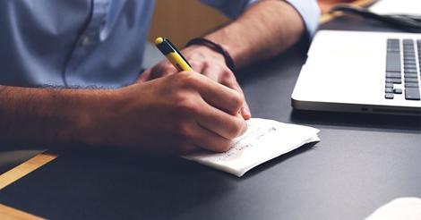 Ein Mann schreibt auf einen Notizblock neben seinem Laptop