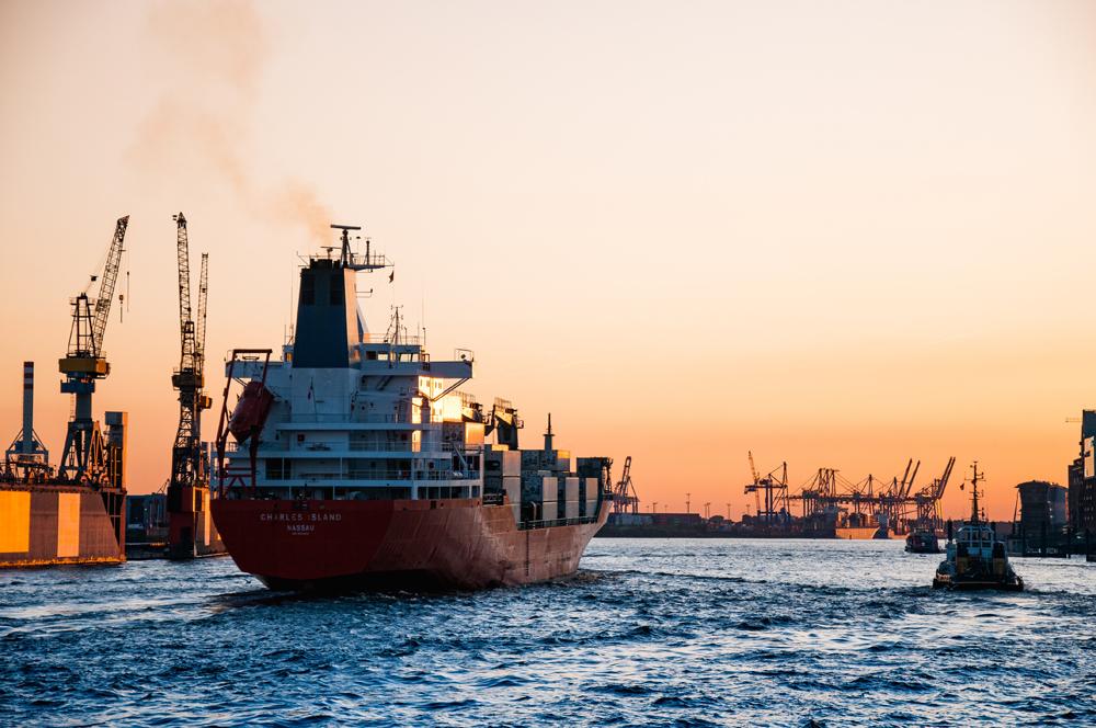 Ein rotes Dampfschiff, welches vom Hafen aufs Meer fährt.