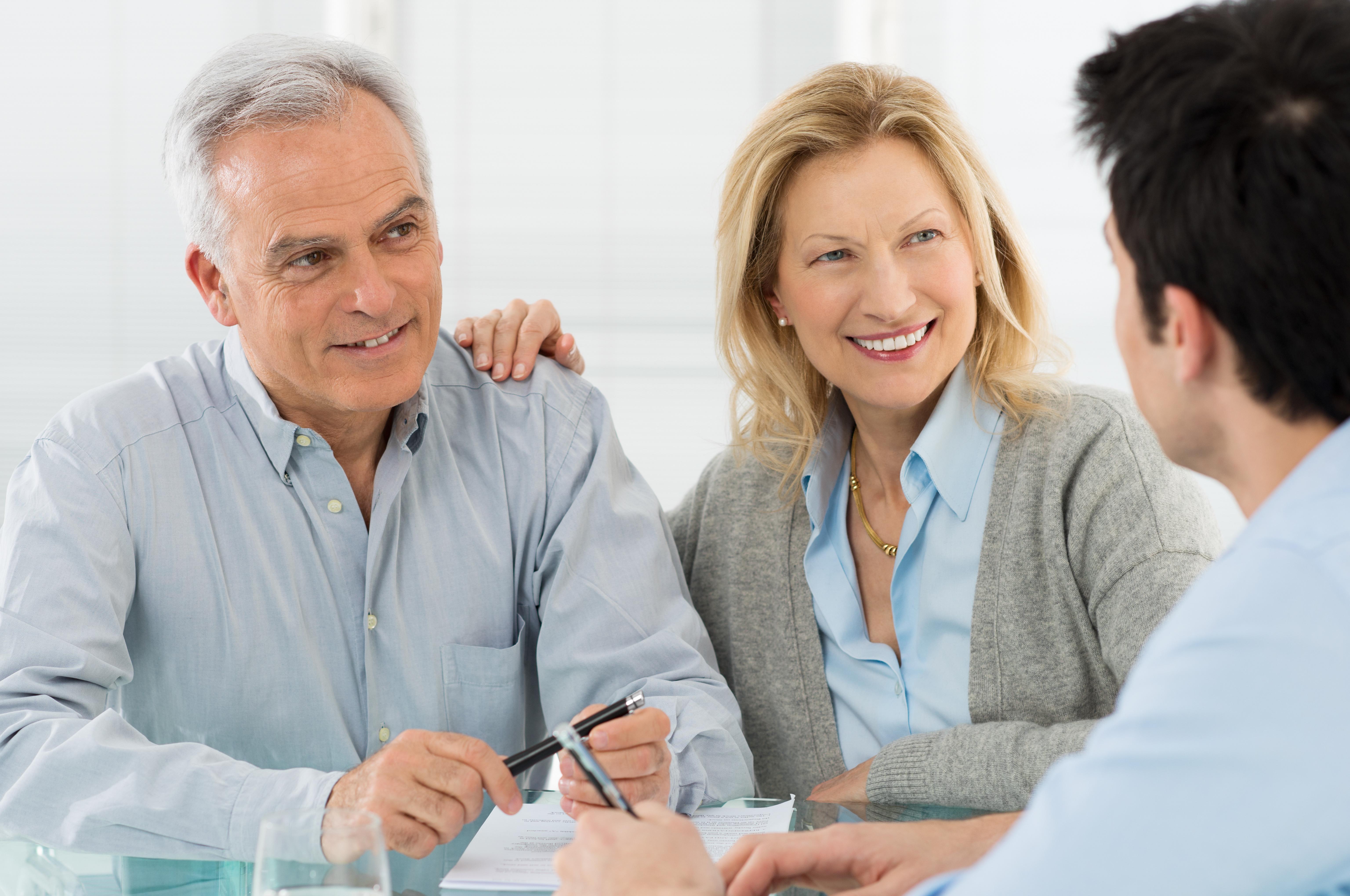 Ein schick gekleidetes älteres Paar blickt lächelnd zu einem Mann in Businesskleidung
