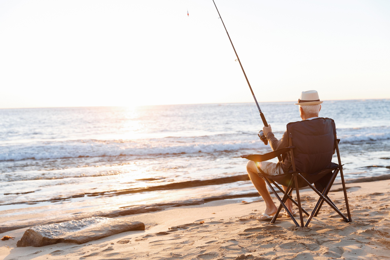 Ein älterer Herr genießt die Rente angelnd am Strand