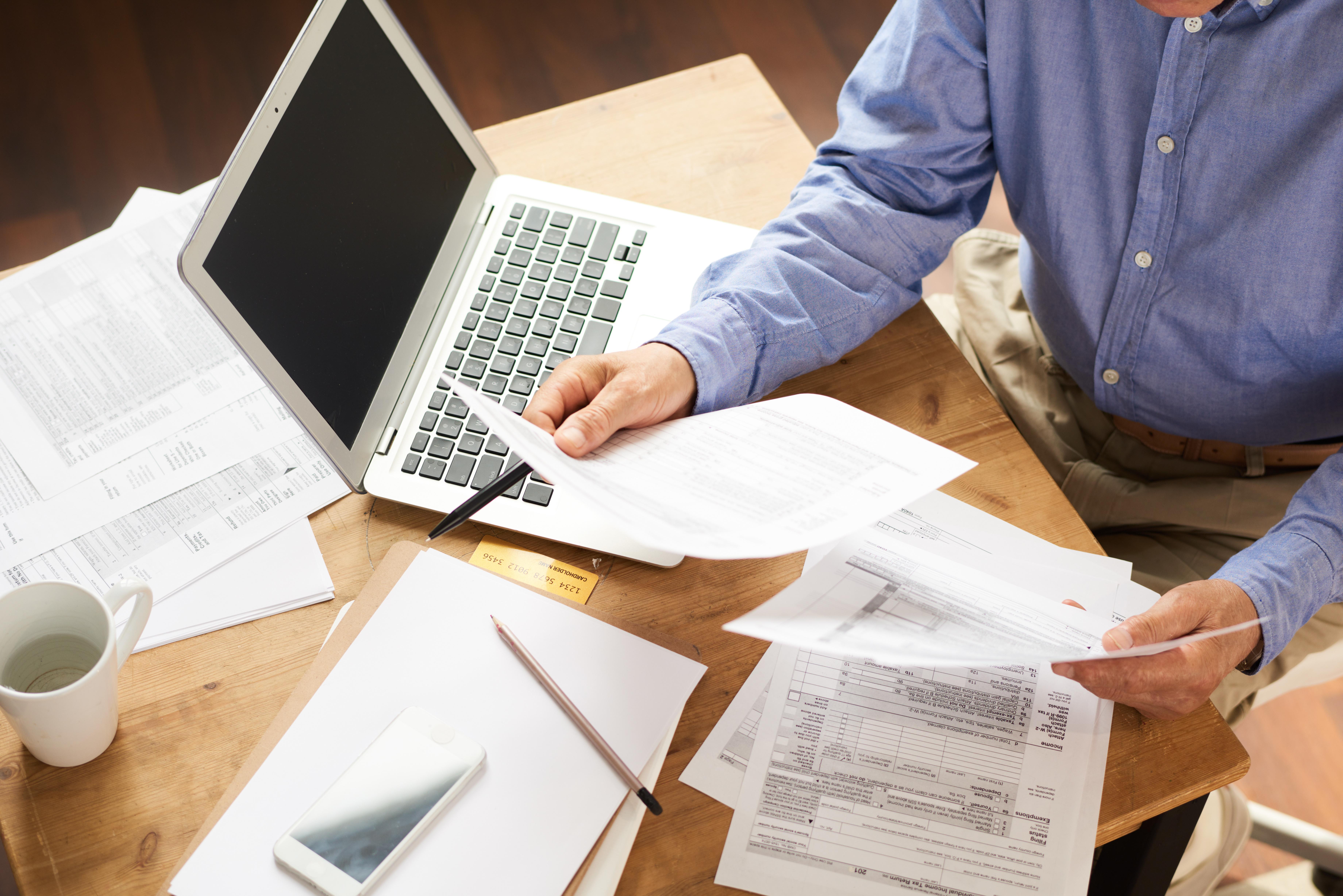 Ein älterer Mann sitzt an einem kleinen Tisch, auf dem ein Notebook, mehrere Zettel, ein Stift, Kaffeetasse und Smartphone liegen. Die Zettel sieht er aufmerksam durch.