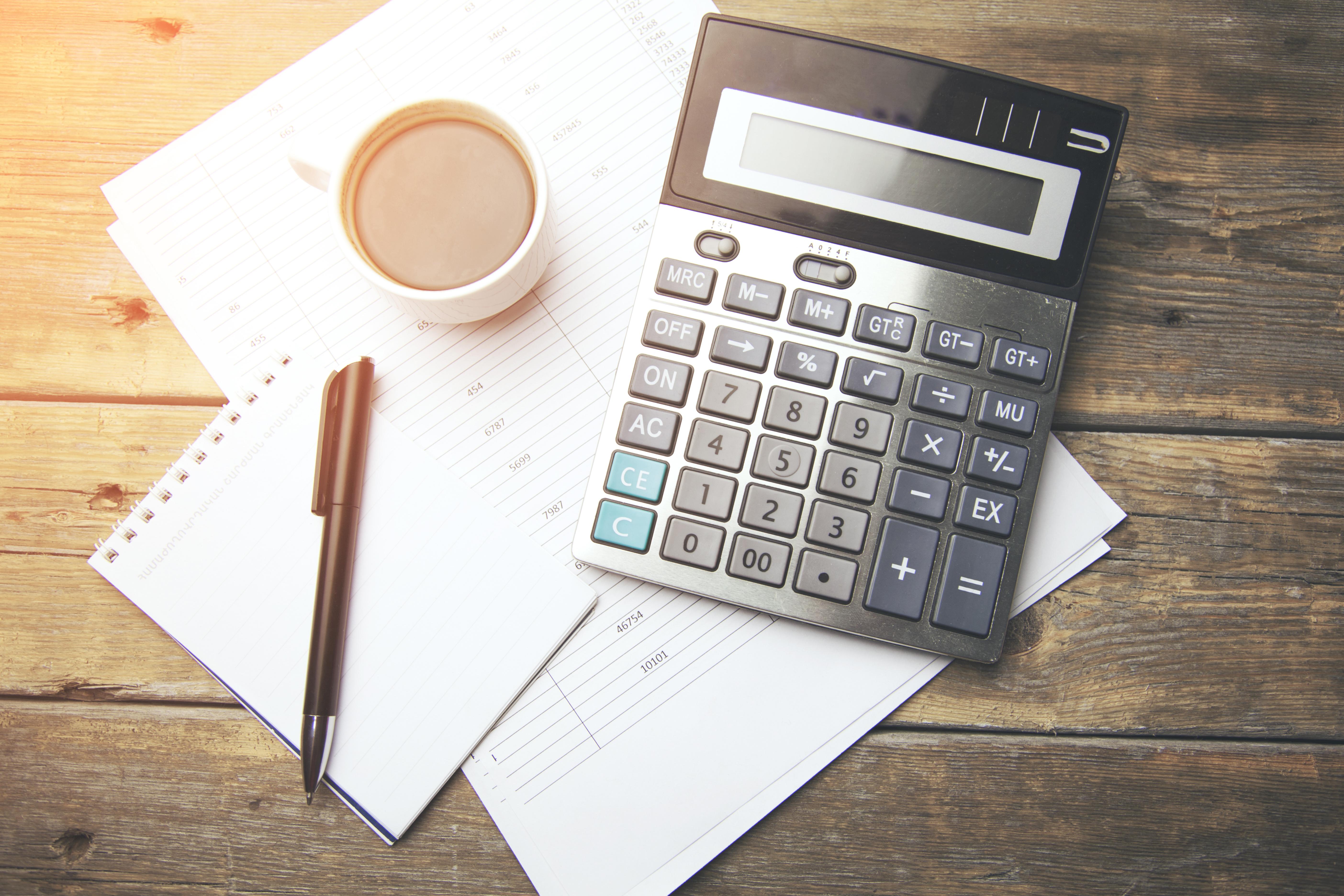 Taschenrechner, Stift, Papier und Kaffeetasse