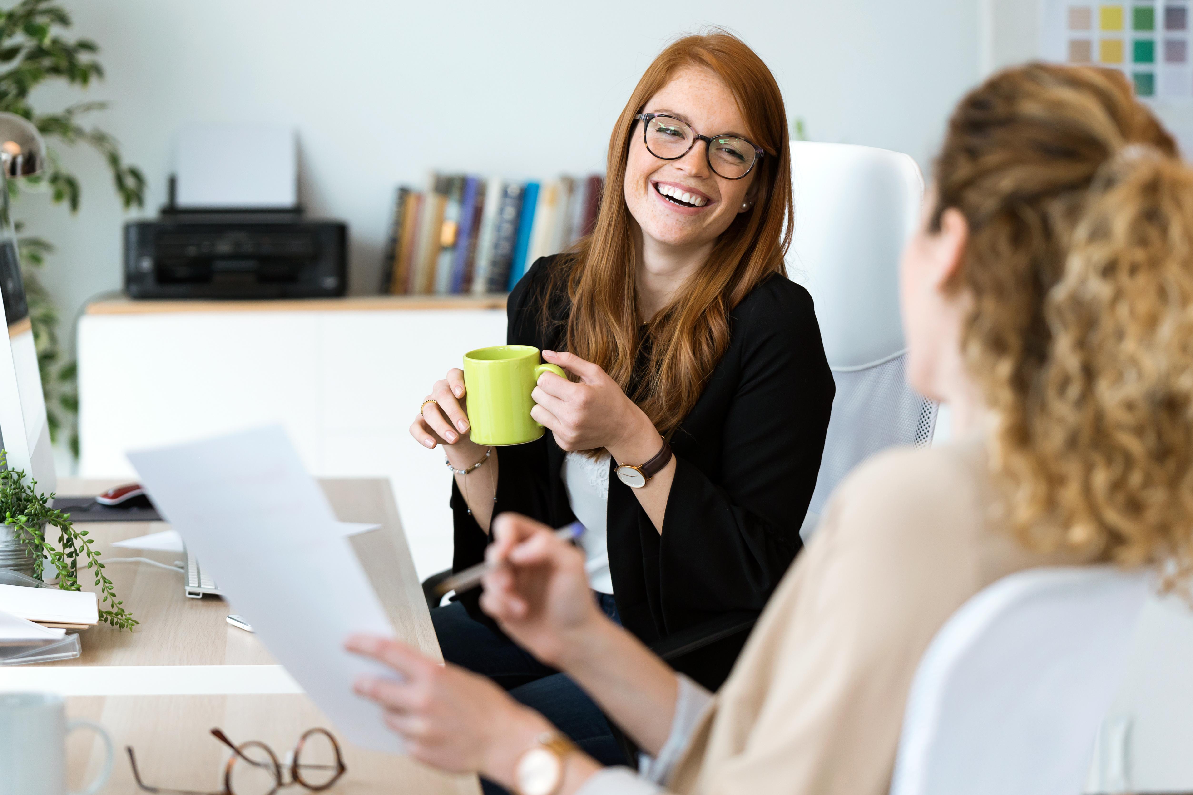 Zwei Frauen sitzen an einem Schreibtisch und unterhalten sich in gelöster Stimmung